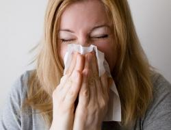 Woman blowing her nose. The common cold is just one of many diseases caused by viruses.  How does a tiny virus cause cold symptoms?